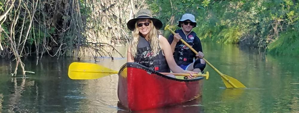 Image of students canoeing down Putah Creek in the Reserve.