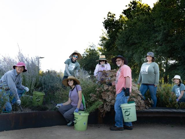 A group of people pose in the Pollinator Garden